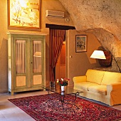 Glass table on Oriental rug in front of yellow couch and simple, rustic, glass-fronted cupboard in interior with rock-like wall