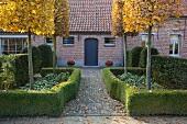 Garten mit formgeschnittenen Bäumen und Hecken vor Wohnhaus mit Ziegelfassade
