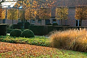 Garten mit formgeschnittenen Bäumen und Büschen vor Wohnhaus mit Ziegelfassade