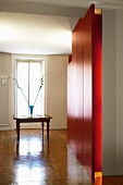 Glossy herringbone parquet in grand hallway with red wall and antique table in front of French window