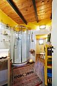 Modernes Bad mit Holzdecke und Duschkabine, davor afrikanischer Teppichläufer auf Parkettboden