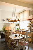 Wooden table and various wooden chairs below rustic pendant lamp in eclectic yet tasteful kitchen-dining room