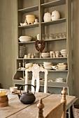 Offenes Geschirrregal - Ton in Ton mit der Wandfarbe und rustikaler Holztisch mit Antikstühlen für gemütlichen Vintagelook in der Wohnküche