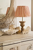 Shabby-chic arrangement of sea shells, marble pots and lamp with fabric lampshade and wooden base on white chest of drawers