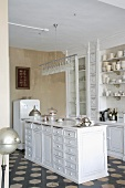 Free-standing, white-painted, country-style wooden counter with drawers below modern pendant lamp and fitted cupboards on vintage tiled floor