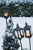 Storm lanterns in garden in winter