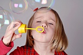 Blond girl blowing soap bubbles