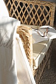Glasses and book on wicker chair