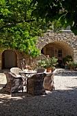 Gartentisch und Rattanstühle auf Kiesboden vor mediterranem Landhaus mit Rundbogen vor dem Eingang