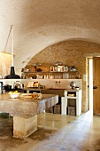 Kitchen table made from massive stone block in rustic kitchen with barrel vault ceiling