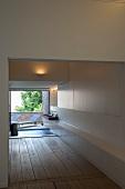Designer-Badezimmer mit Holzdielenboden und offene Terrassentür mit Blick auf Liegen