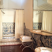 Vintage bathtub with traditional white and blue wall tiles and shower curtain in front of bathtub
