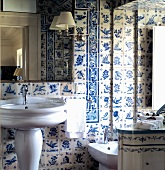 Traditional bathroom with pedestal sink against white and blue wall tiles and mirror lamp with white shade