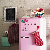 Pink fridge against brick wall