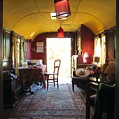 Cosy interior of converted railway carriage with Oriental rug and red lanterns hanging from yellow ceiling