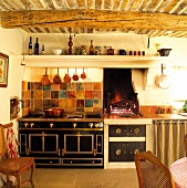 Mediterranean kitchen with brick ceiling and round beams above stylish retro cooker and open fireplace