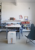 Selbstgebauter Tisch aus Gerüststangen vor halbhohem Regal in minimalistischem Wohnraum