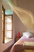 Schlichtes Schlafzimmer - Rosa Tagesdecke auf Bett vor offenem Fenster mit wehendem Vorhang