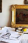 Artist's studio: original paintings, painters' utensils and gilt-framed oil painting on table