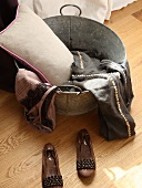 Ladies' shoes next to cushion and clothes in zinc tub on wooden floor