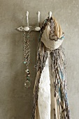 Fringed scarf and necklace hanging from clothes pegs on concrete wall
