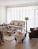 Ledersessel mit passendem Fussschemel und Rokoko Sofa vor geschlossenen Vorhängen am Fenster in schlichtem Wohnzimmer