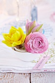 Double narcissus, pink ranunculus and tulip as table centrepiece