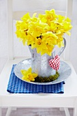 Bouquet of narcissus in zinc pitcher with moss wreath and small fabric heart