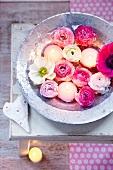 Rosa und weiße Ranukeln, Anemonen und Schwimmkerzen in einer Zinkwanne