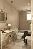Vintage-Bad mit antikem Schminkmöbel als Waschtisch für das Einbaubecken; modernes WC im Kontrast zu Wänden in heller Marmor-Spachteltechnik