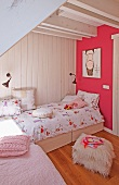 Bright child's bedroom - flokati pouffe in front of bed against white wooden wall and pink-painted wall