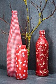 Bottles covered with red and white patterned paper as ornaments and branch leaning against grey wall