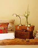 Vase of flowers and retro table lamp on stack of vintage-effect suitcases next to ethnic scatter cushion on floor cushion