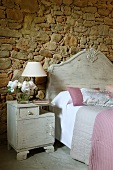 Bedside cabinet painted light grey next to bed with headboard of same colour against stone wall