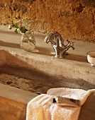 Concrete wash basin with vintage tap fittings against rustic wall