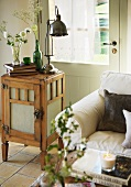Upholstered couch and retro table lamp on small wooden cabinet in front of back door