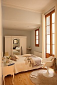 Narrow bedroom with eclectic mixture of furniture styles from Rococo bedside table to fifties shell chair and rustic wardrobe