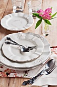 Dinner Plates and Silverware on a Wood Table; Pink Flowers in a Bud Vase