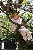 Girl sitting in a tree in garden