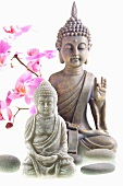 Stone and metal Buddha figurines with orchid sprig