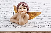 Angel figurine lying on sheet music