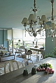 Vintage chandelier with glass ornaments above dining table in front of work station and lounge area in open-plan living room with traditional ambiance