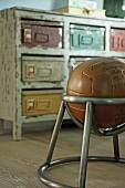 Leather ball in metal chair frame in front of vintage chest of drawers with metal boxes in place of drawers