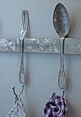 Rusty hook rail with cutlery motif and partial view of tea towels hanging from hooks