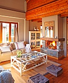 Living area with coffee table made of pale wooden slats and comfortable sofa in front of country-style open fire