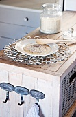A plate with grains of rice and a decorative metal trivet on a rustic shelf unit with metal wall hooks