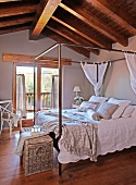 Four-poster bed with metal frame and white bed linen in attic room with rustic wood-beamed ceiling