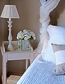 Table lamp and bouquet on rustic bedside table next to bed with scatter cushions
