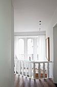 Diele mit weiss lackiertem Holzgeländer zu offenem Treppenaufgang; Rundbogenfenster mit kleinem Gartenzwerg im Hintergrund