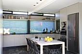 Designer dining table and black, Bauhaus shell chairs in contemporary kitchen